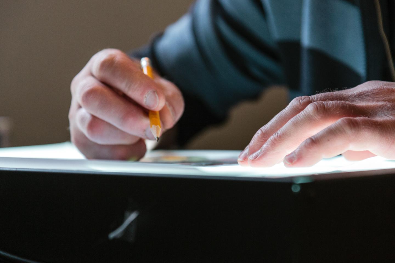 Nærbilde av hender som holder en blyant over et papir. Foto.