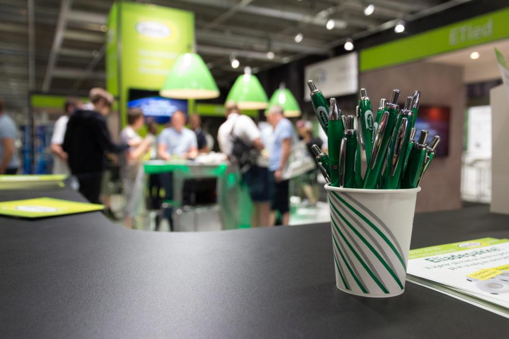 En kopp med penner i forgruppen, og en rekke med mennesker som sitter rundt et bord i bakgrunnen. Foto.