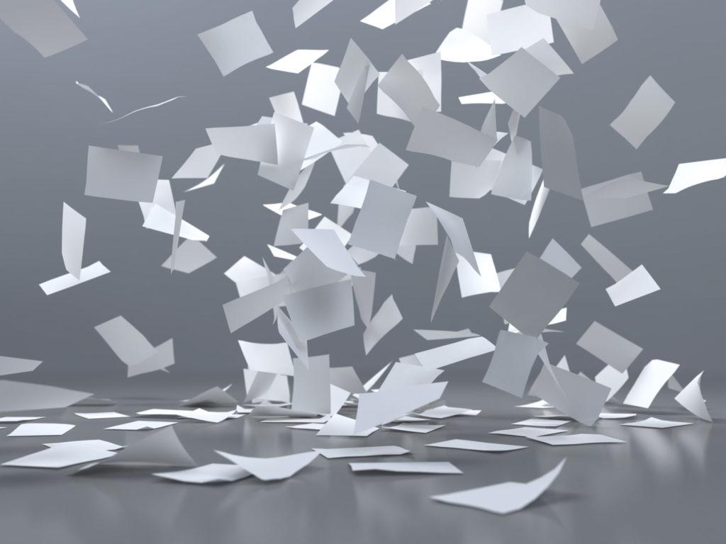 En virvelvind av papirer som faller ned på bakken. Foto.