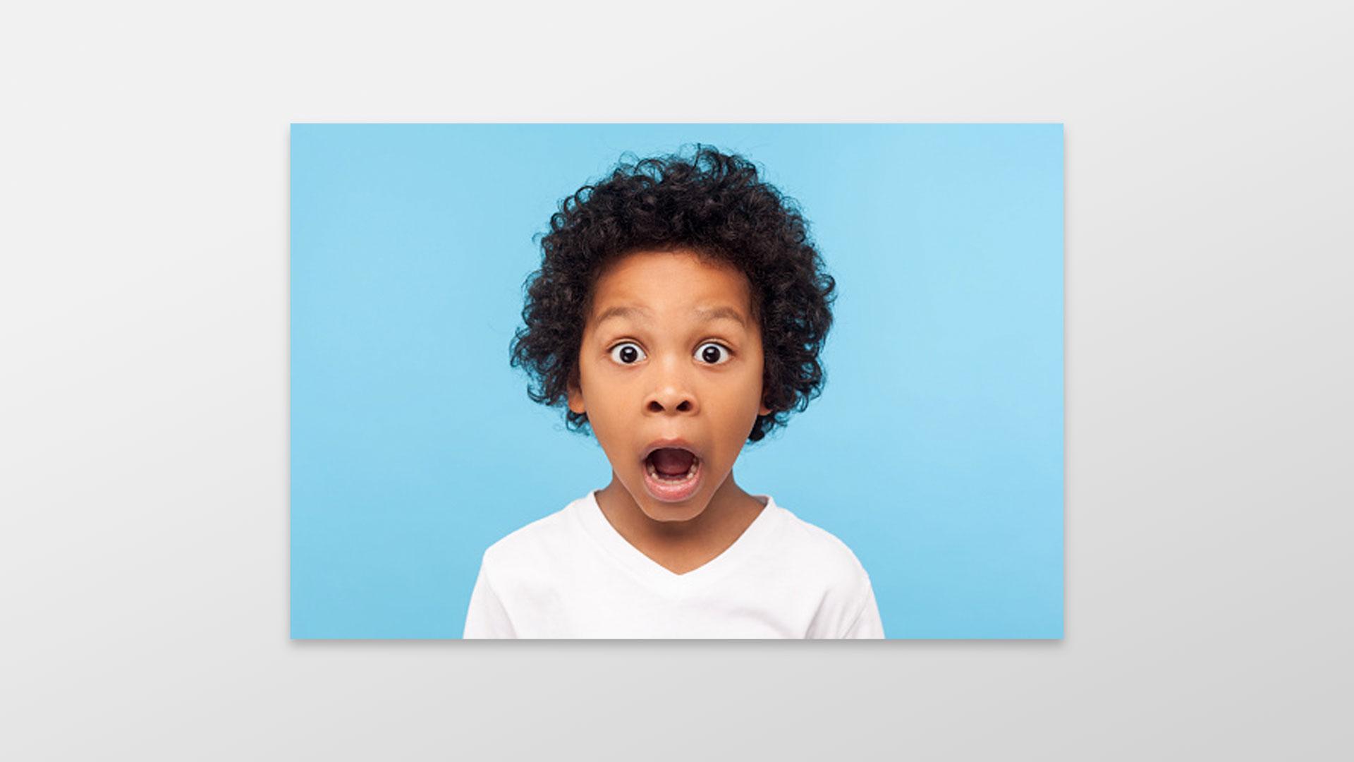 Stockbilde av en forskrekket gutt, med blå bakgrunn. Foto.