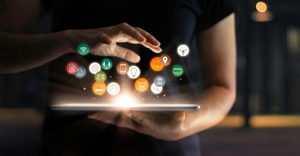 En nærbilde av en person som holder en Ipad, som det strømmer digitale symboler ut av. Foto og illustrasjon.