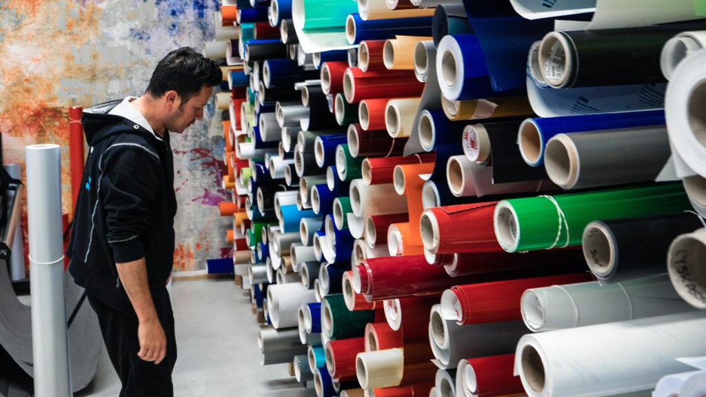 En produksjonsmedarbeider som ser på en vegg full av folieruller. Foto.