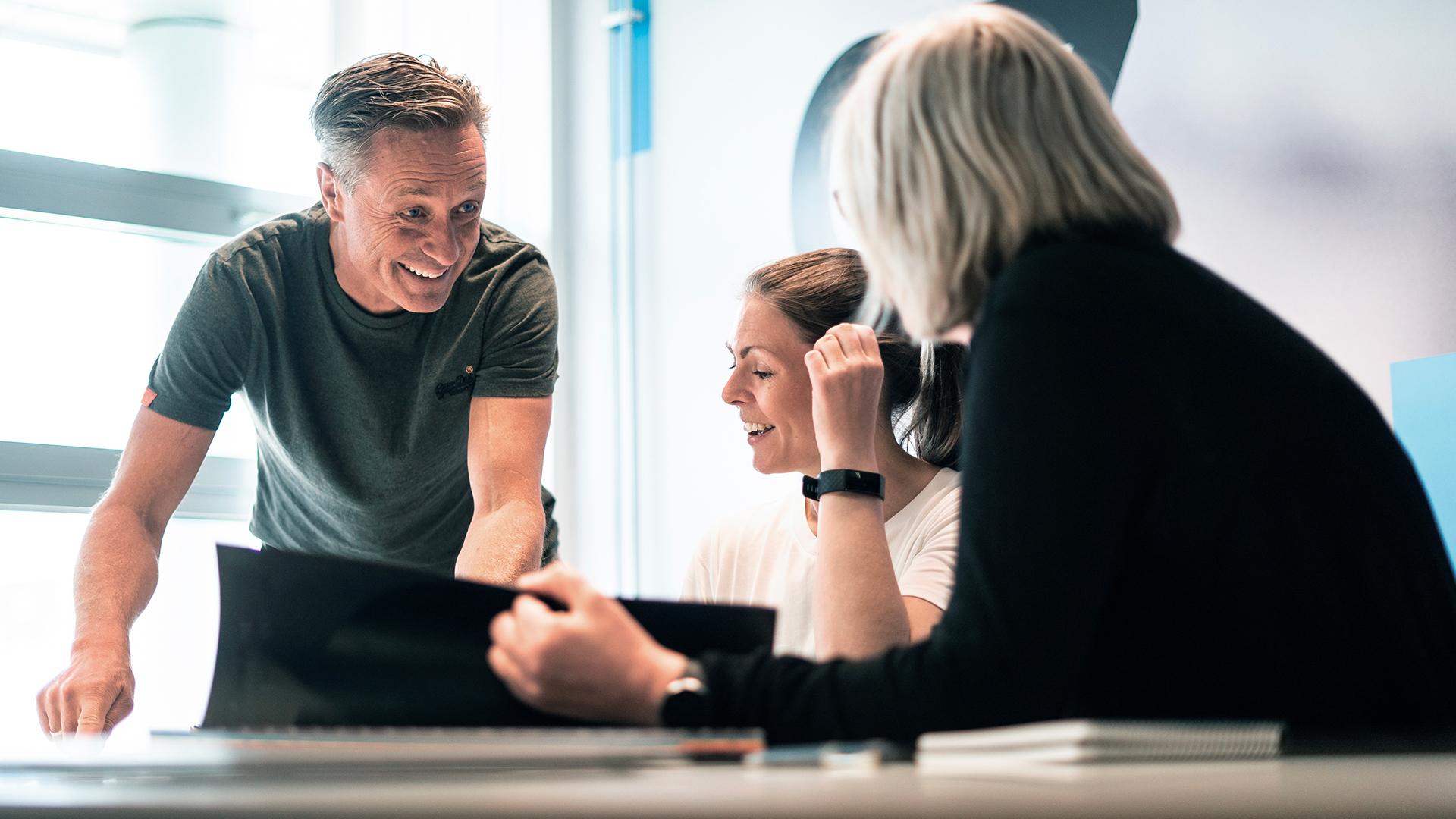 Mennesker jobber sammen på et møterom. Foto.