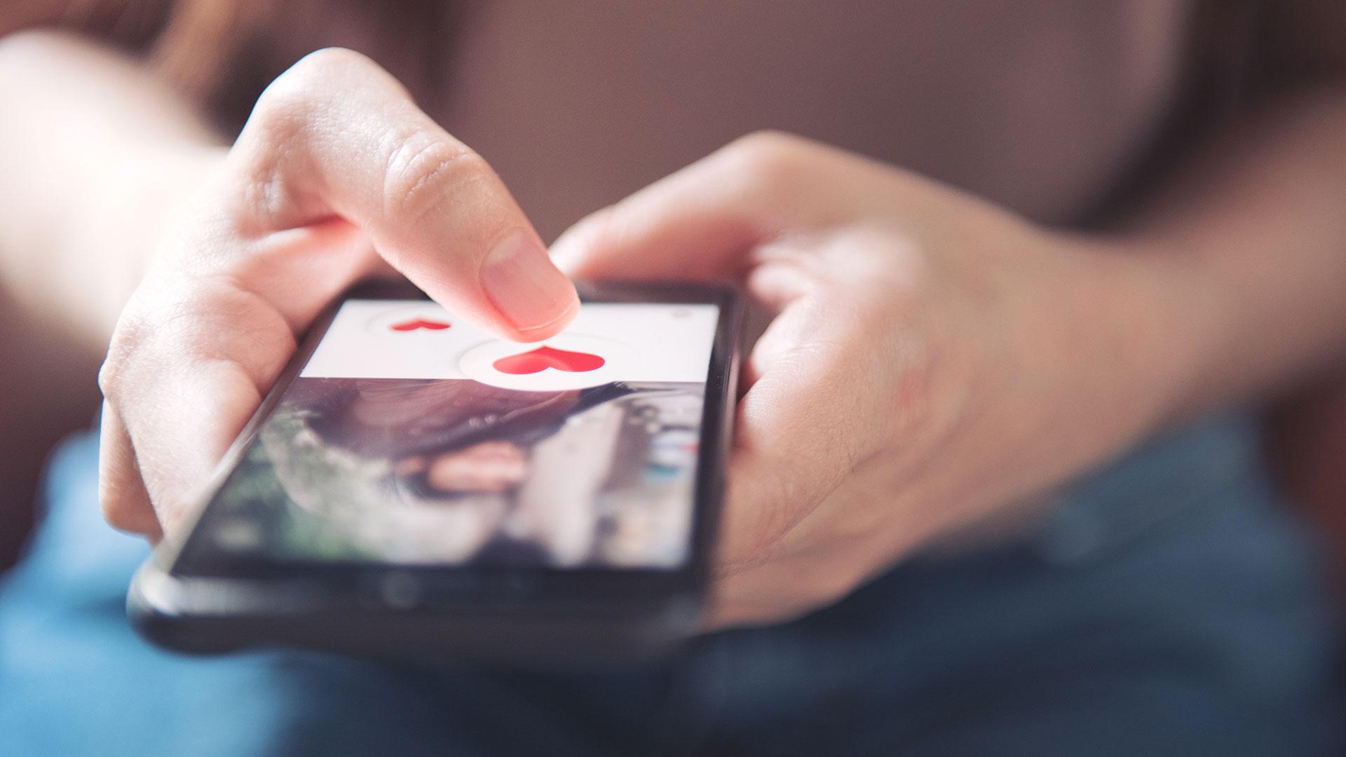 Kvinne trykker hjerte-ikon på sosiale medier på mobil